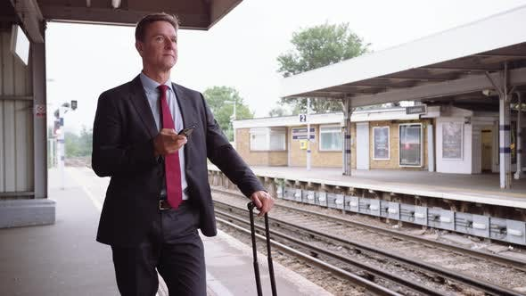 Thumbnail for Businessman waiting for delayed train on platform