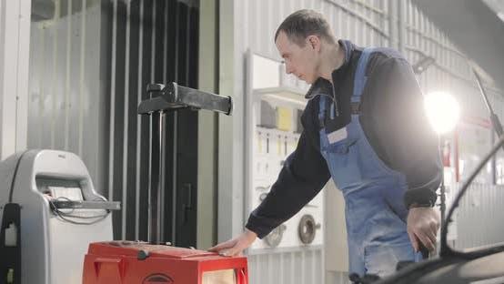 Thumbnail for Autoservice. Mechaniker stellt Scheinwerfer ein. Abblendlicht, Fernlicht. Epischer Schuss