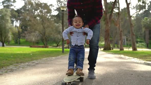 African American Young Father Holding Son on Skateboard in Park