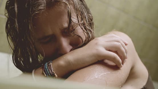 Depressed Young Woman Crying In Bath