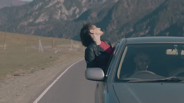 Lady with Dark Hair Leans Out of Speeding Car Window