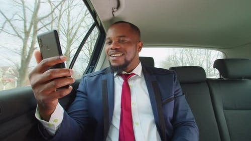African Male Entrepreneur Video Conferencing on Cellphone in Vehicle