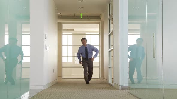 Thumbnail for Businessman walking down office hallway with confidence