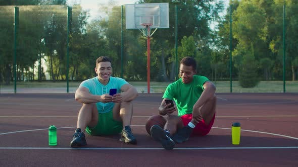Thumbnail for Athletes with Phones Resting on Basketball Court