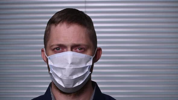 A young Caucasian man in mask are staying safe in the coronavirus epidemic