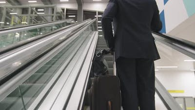 Business Man With Suitcase On Escalator