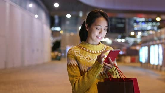 Thumbnail for Woman use of mobile phone in city and hold with shopping bag at night