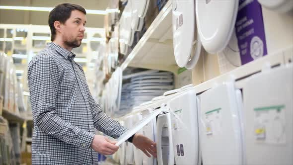 Man Selecting Toilet Seat in the Home Improvement Store