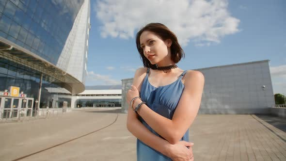Thumbnail for Sad Young Woman Posing With Industrial Background And Glass Buildings
