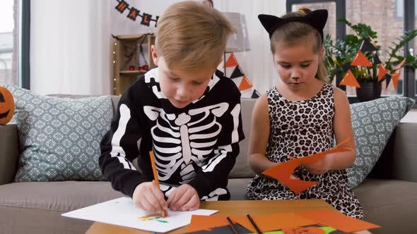Kids in Halloween Costumes Doing Crafts at Home