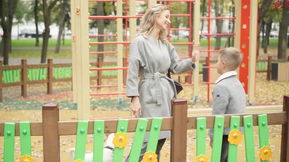Wide Shot Portrait of Happy Caucasian Beautiful Mother Enjoying Autumn Weekend in Park with Son and