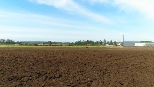 Thumbnail for Wide Shot of Agricultural Tractor Furrowing Fertile Field on Sunny Spring Day