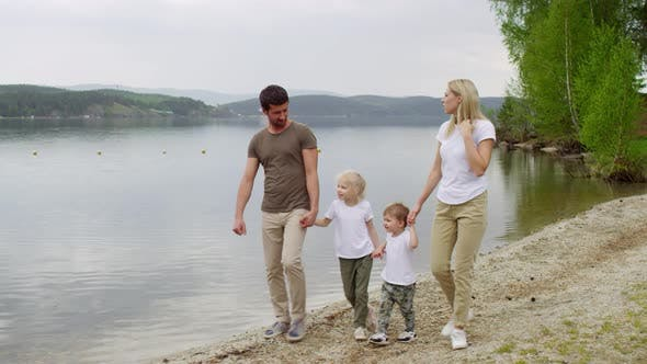 Family Walking by the Lake and Enjoying Scenery
