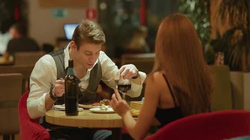 Guy with the Girl Have a Good Time in a Cozy Cafe, Chatting and Laughing. Romantic Meeting of a