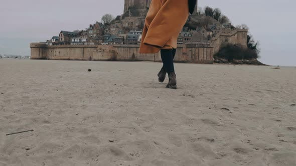 Cinematic Move Up on Fashionable Happy Travel Blogger Woman Walking on Soft Sand at Epic Mont Saint