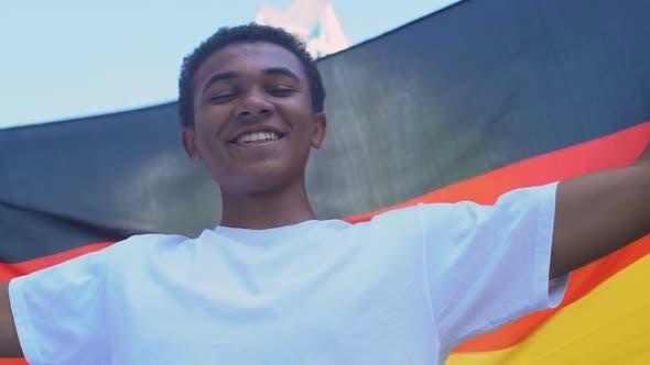 Afro-American teenager boy waving German flag outdoors