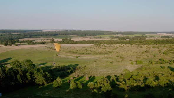 Thumbnail for Aerial Drone View Shot of Mechanical Hang Glider Flying on Nature on Rural Village Countryside