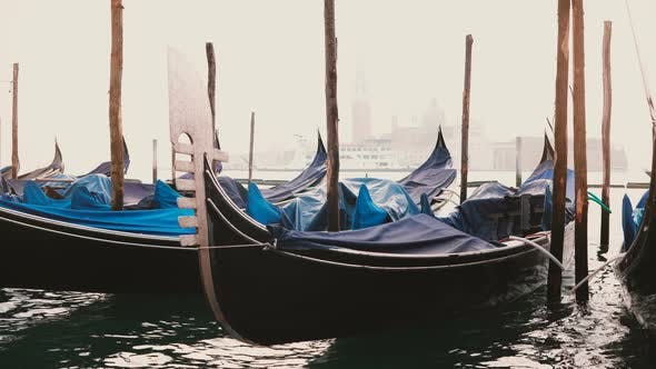 Thumbnail for Atmospheric View of Beautiful Traditional Gondolas Rocking on the Waves at Foggy Wooden Lagoon Pier