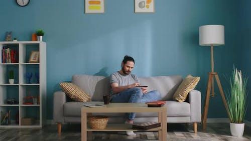 Mann zeichnet Im Gemütlichen Wohnzimmer