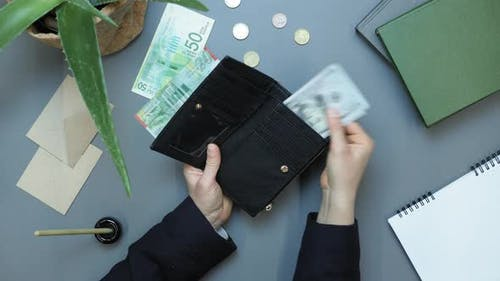 Woman opening wallet, pulling out cash money and counting them