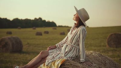 Young woman in hat sits on a haystack