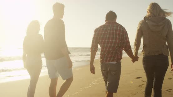 Thumbnail for Couples walking on the beach holding hands