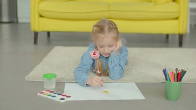 Little Girl Painting with Paintbrush and Paints