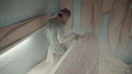 Worker Polishing Surfboard Blank with Automatic Polisher
