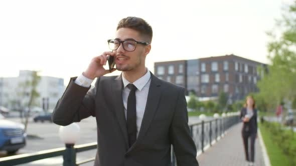 Thumbnail for Businessman in Glasses Talking on Phone Outdoors