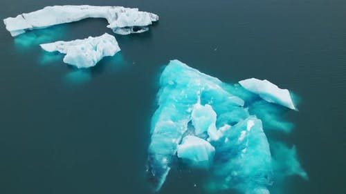 Breathtaking Drone Shot of an Iceberg Melting and Floating in Blue Water
