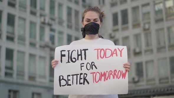 Thumbnail for Schöne Frau in Gesicht Maske stehend in Urban City mit Banner und Blick auf die Kamera