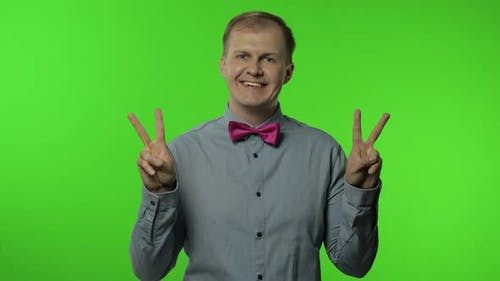 Man Showing Victory Sign, Success and Win, Peace Gesture and Smiling with Kind Optimistic Expression