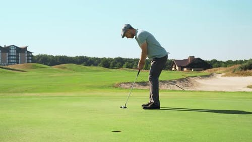 Concentrated Golf Player Hitting Ball To Hole, Playing Golf Outdoor at Course