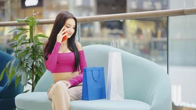 Turkish Woman Chatting on Phone After Shopping