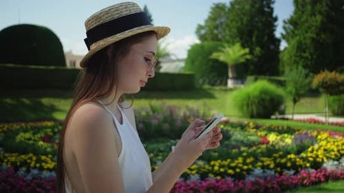 Girl Tourist Using Mobile in the Park of Lednice Palace Czechia