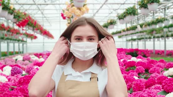 Woman Remowing Mask for Breathing Among Colorful Hydrangeas