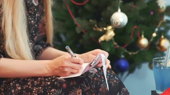 Thumbnail for Close Up Hands of Female Writing Letter on Knees at Christmas Eve