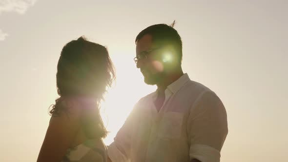 Cover Image for Silhouettes of Man and Woman Kissing Against the Sky in a Hot Sunny Day