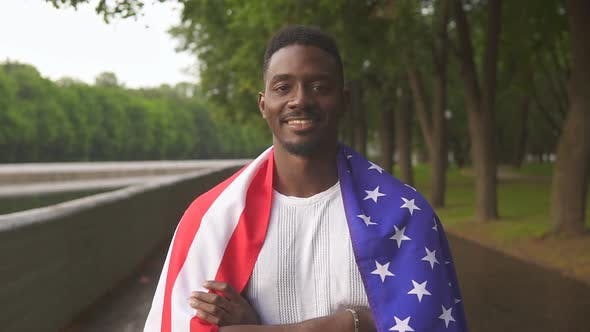 Portrait of happy patriotic african american man holding US flag slow motion