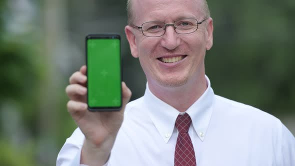 Thumbnail for Happy Mature Bald Businessman Showing Phone Outdoors
