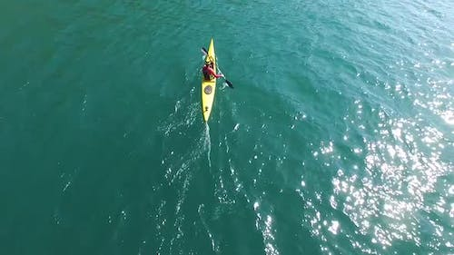 A kayaker paddles in a scenic mountain lake with a drone hovering above him.