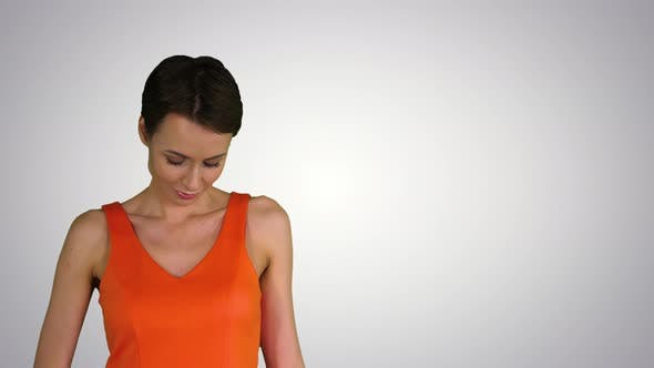 Thumbnail for A Beautiful, Cheerful Woman Straightens Her Dress on Gradient Background