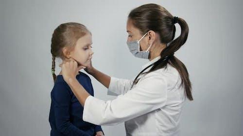 Arzt palpiert Lymphknoten am Hals des kleinen Mädchens