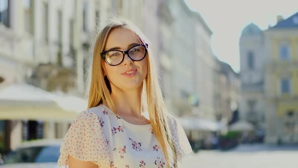 Thumbnail for Gorgeous Happy Woman with Straight Hair in the Glasses Smiling on the Camera on the Street