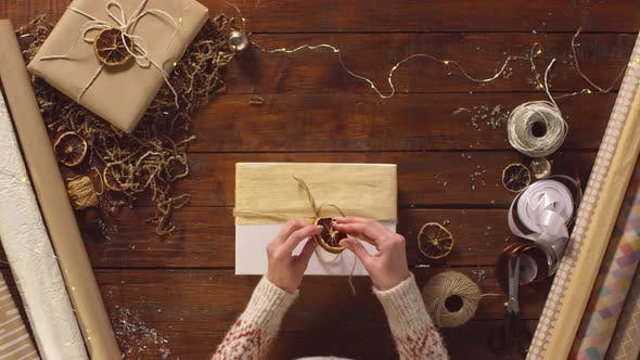 Thumbnail for Female Hands Decorating Xmas Present with Rope and Dried Orange Slice