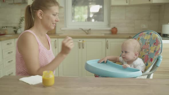 Thumbnail for Mother Woman Feeding Baby Her Kitchen Table Spoon