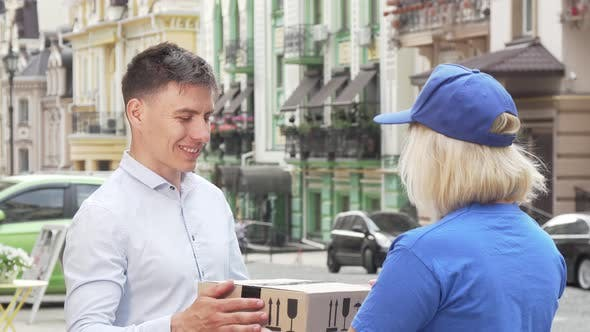 Thumbnail for Handsome Man Examining Package Delivered By Female Courier