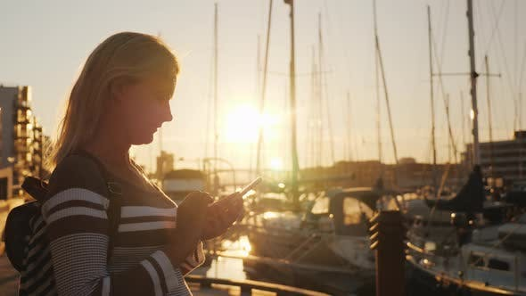 Thumbnail for Silhouette of a Woman Using a Smartphone Near the Pier Where Many Yachts Are Moored
