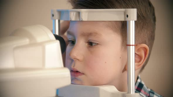 Thumbnail for A Little Boy Having a Treatment in Eye Clinic - a Little Boy Looking Through the Lens in the Device