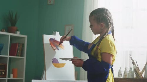 Girl In Blue Apron Is Painting